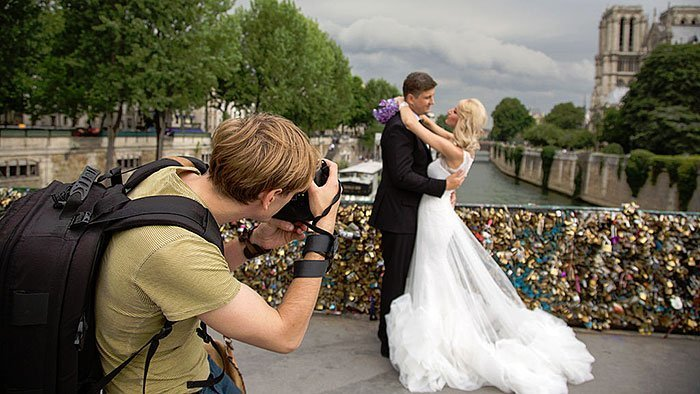 Image Showing A Wedding Photographer Photographing A Wedding Couple In A Floral Decoration Background.